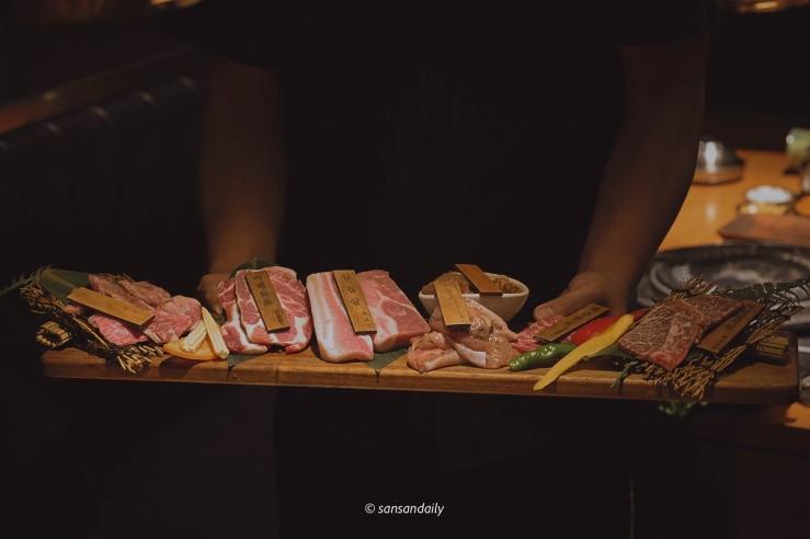 男子端著一盤長長的燒肉生肉片