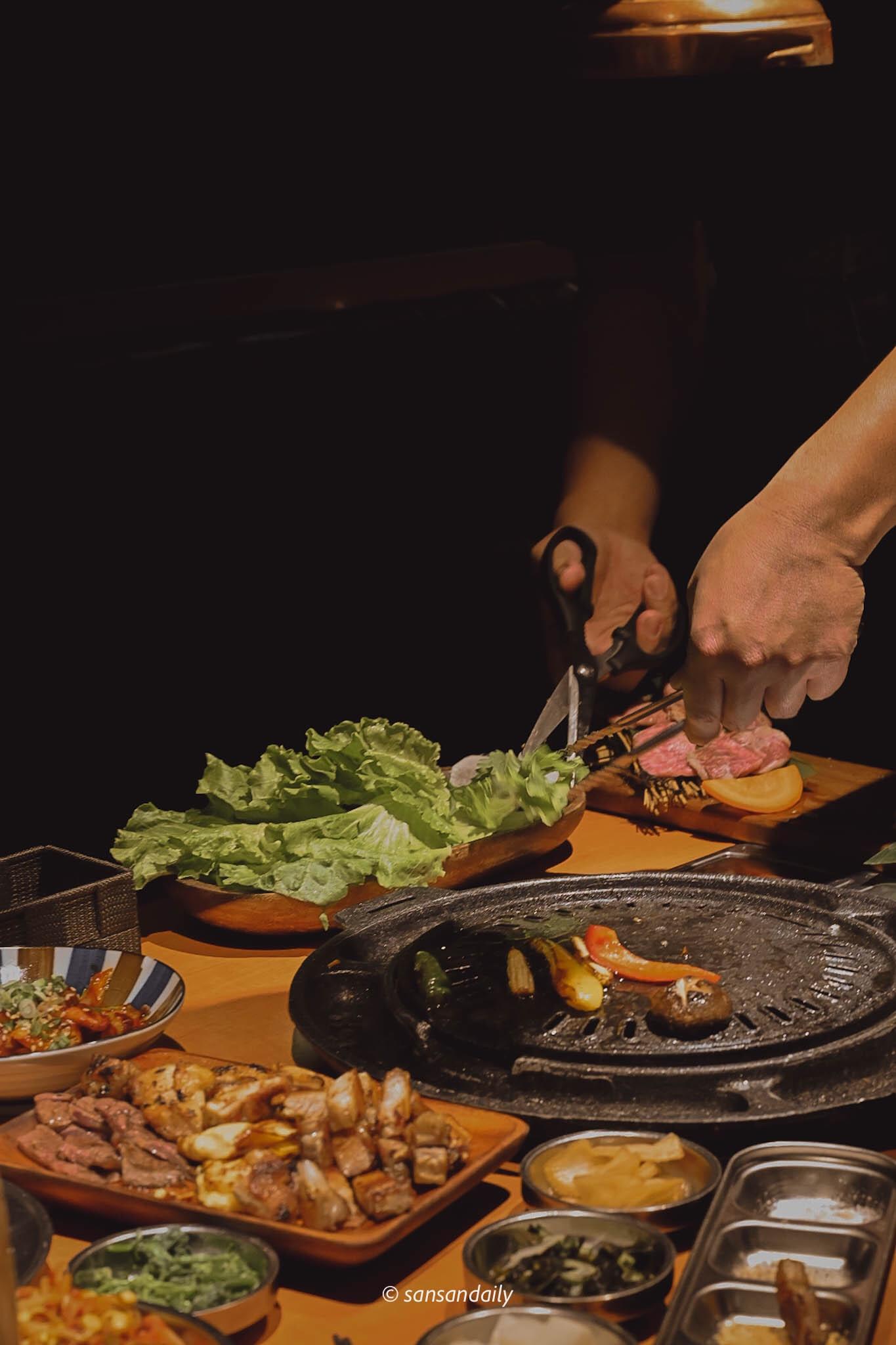 餐桌上一個人用剪刀剪生菜
