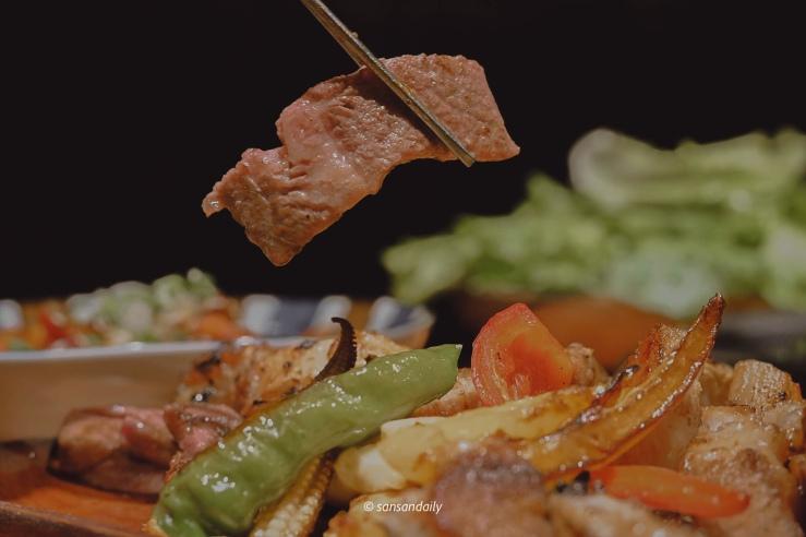 筷子夾起一片烤好的和牛翼板肉