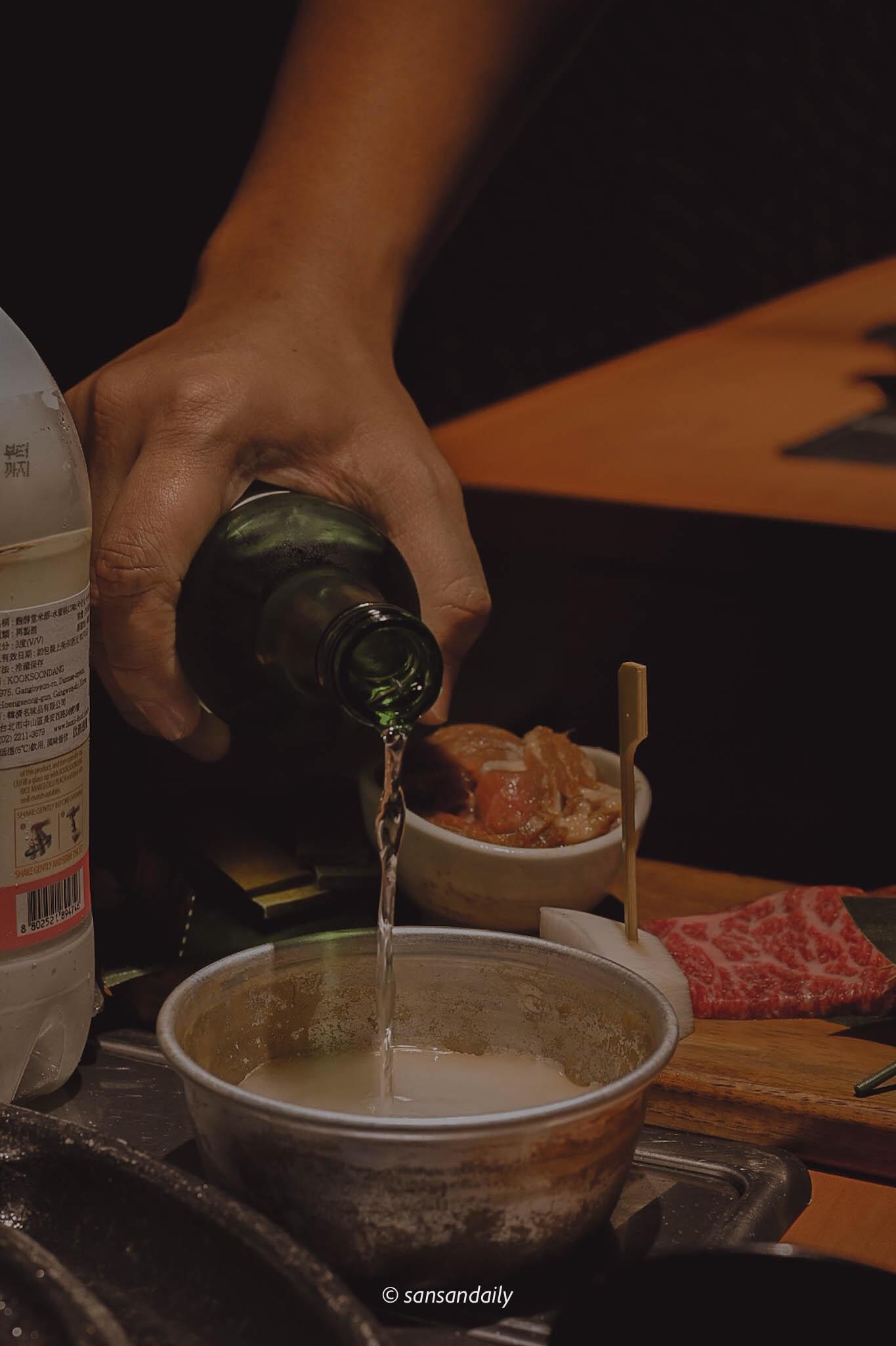 一個人將真露燒酎倒入在桌上的鋁碗