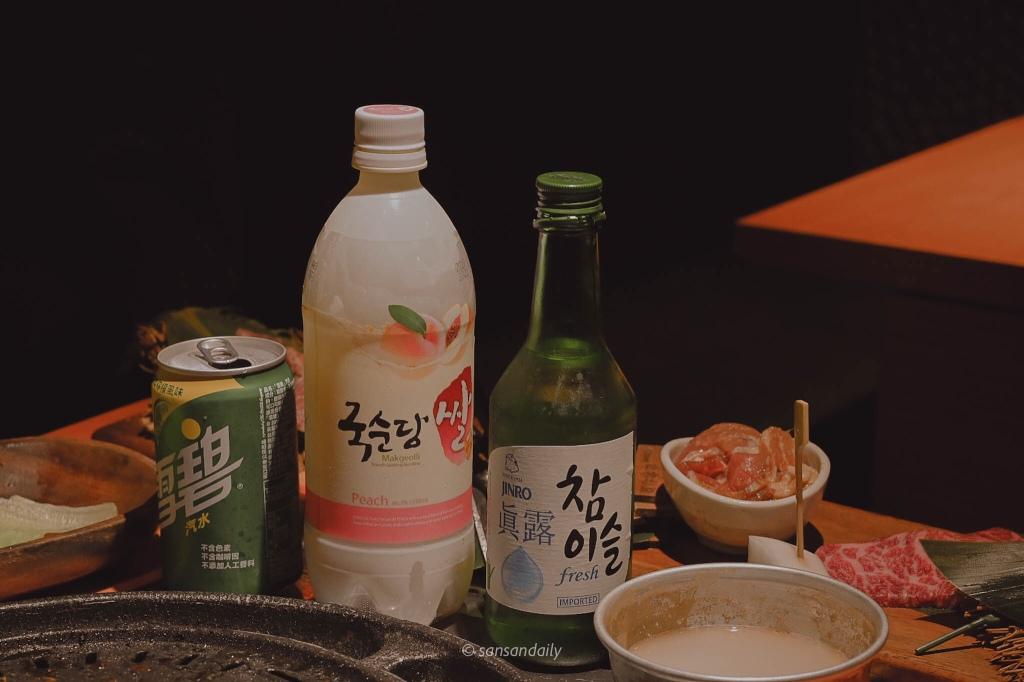 桌上擺著一瓶雪碧、水蜜桃口味馬格利以及真露燒酎