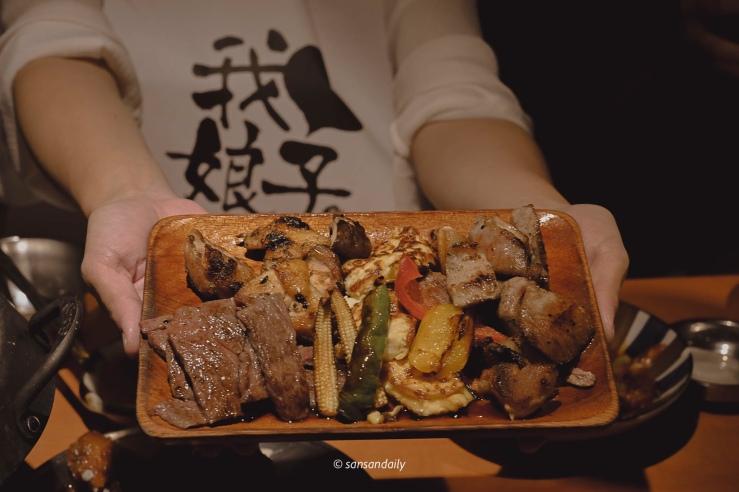 一位美女端著裝有燒烤和烤蔬菜的木盤
