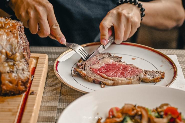 一位男子拿刀叉切著Mr.Tom爐烤肋眼牛排