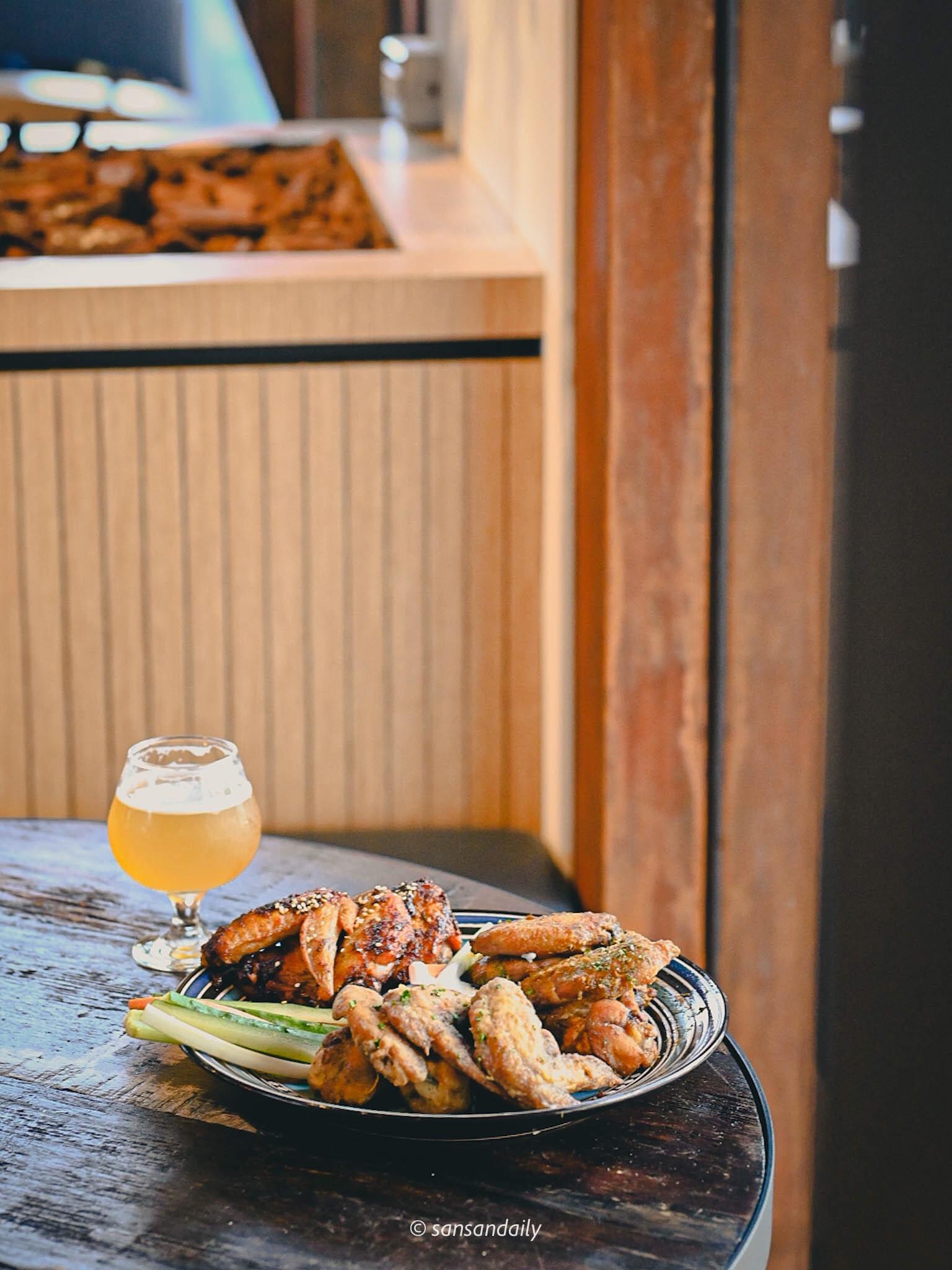 桌上一杯啤酒一盤GUMGUM Beer & Wings剛剛有三寶雞翅