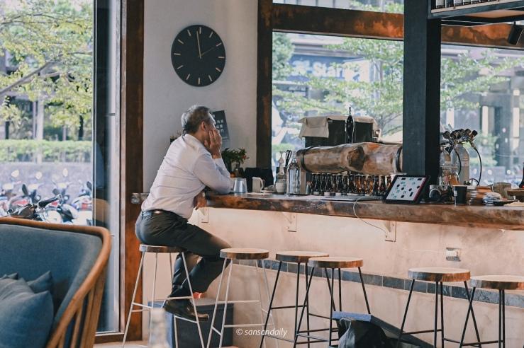 一位穿白襯衫男子坐在GUMGUM Beer & Wings吧台區情境圖