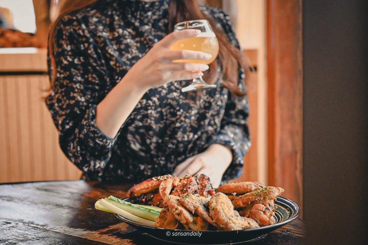 一位女子在GUMGUM Beer & Wings手拿高酒杯啤酒 桌上一盤雞翅