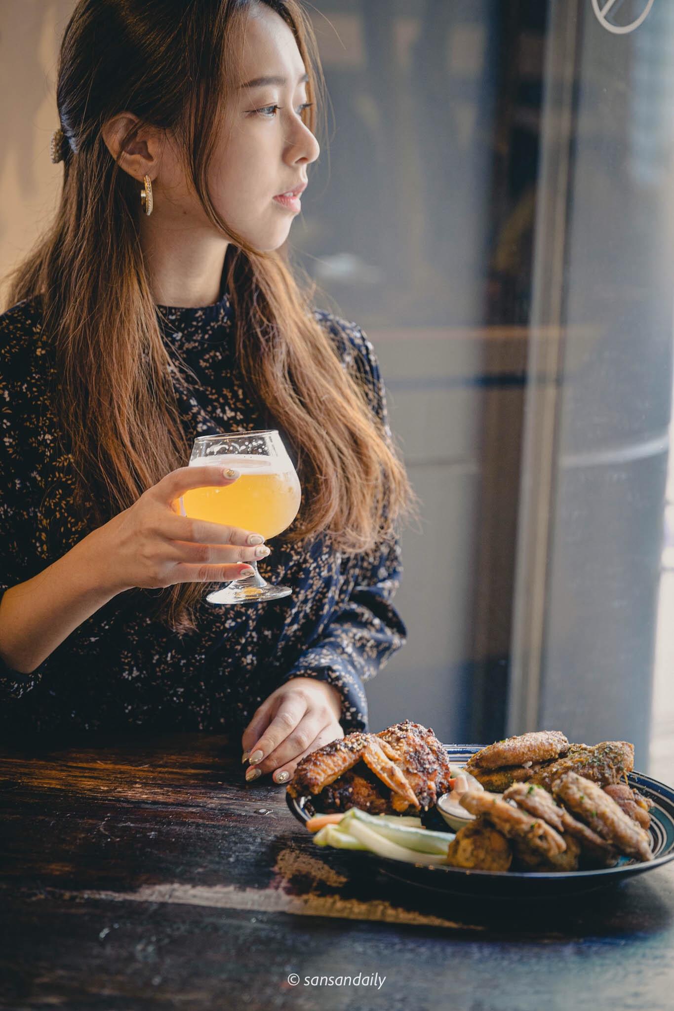 一位女子手拿高腳杯啤酒看向窗外情境圖